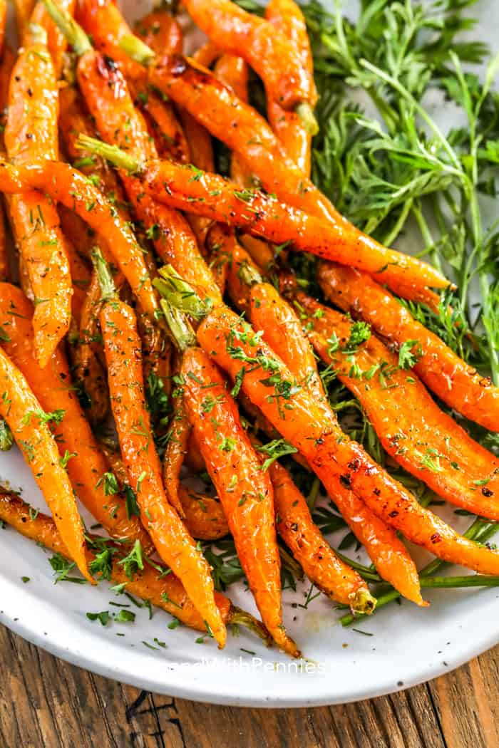 close up of a plate of honey roasted carrots garnished with parsley and dill.