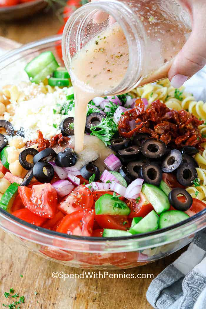 Mediterranean Pasta Salad with dressing being poured on top.