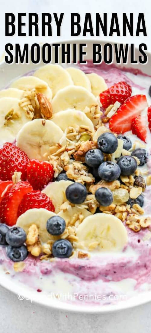 Banana berry smoothie bowl garnished with bananas, strawberries and blueberries.