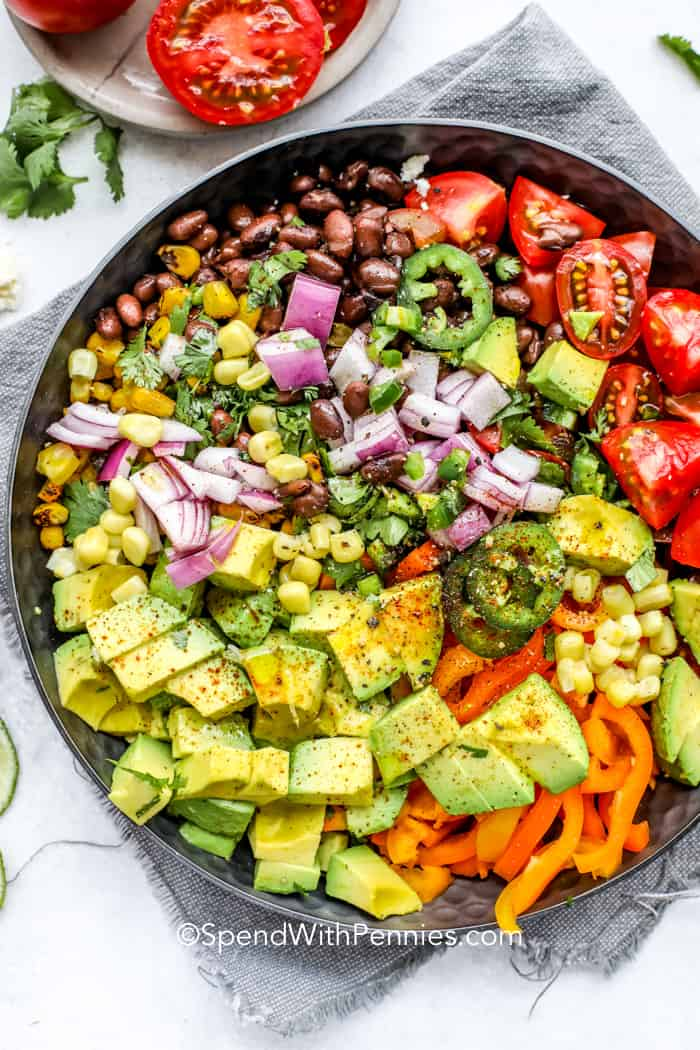overhead of a serving dish with Southwest Avocado Salad including corn, jalapeño, peppers, avocado, lime, onion, beans and cheese