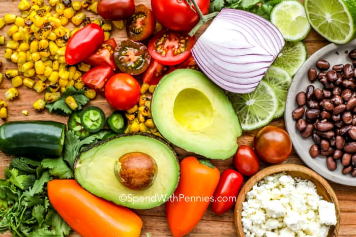 Southwest Avocado Salad ingredients on a cutting board including avocado, corn, peppers, tomatoes and onion