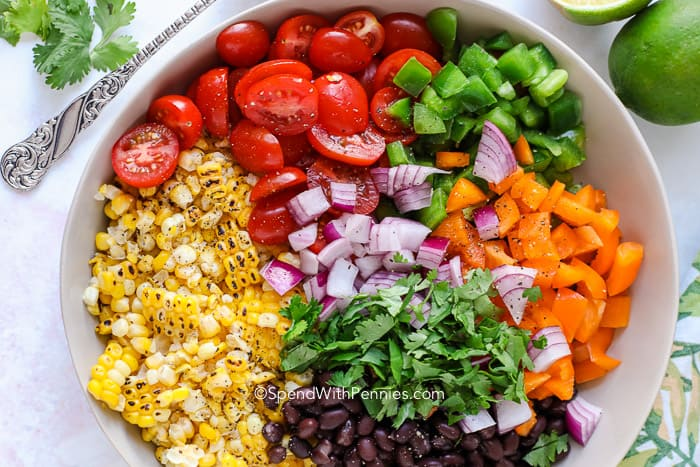 Salad ingredients assembled in a grey bowl ready to be tossed together.