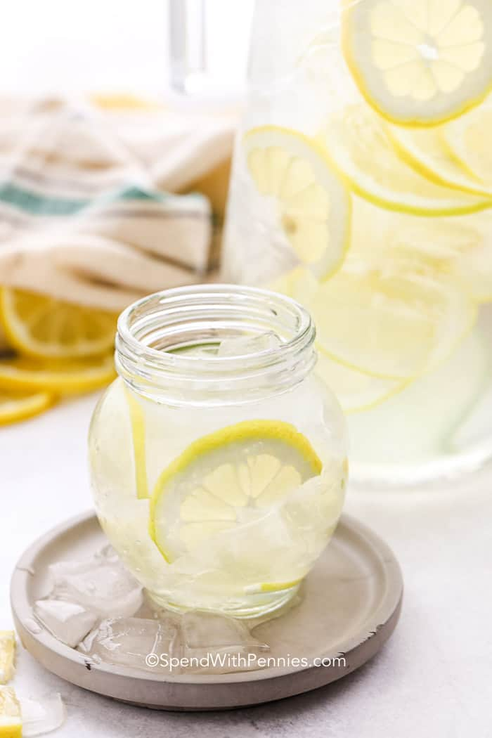Small glass of Lemon Water with a big jar of it in the background