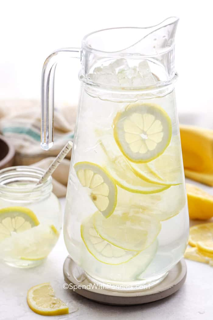 Big glass jar of Lemon Water with small glass next to it