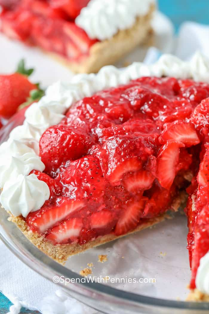 A no bake strawberry pie in a pie pan with a slice removed.