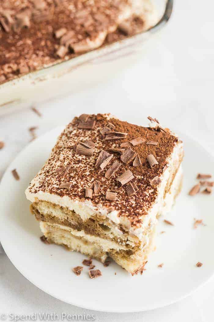 close up slice of tiramisu garnished with cocoa and chocolate on a white plate with a pan of tiramisu in the background