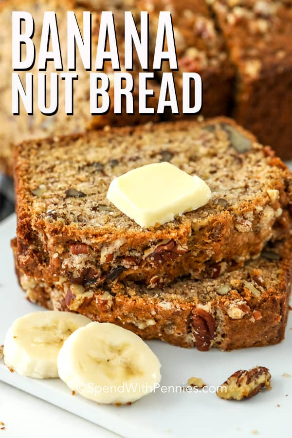 Two slices of banana nut bread stacked on a plate with a pat of butter on top.