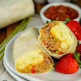 Breakfast burrito on a plate cut in half with strawberries on the side