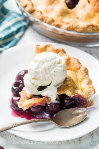 piece of homemade cherry pie with ice cream on a white plate with a spoon with the whole pie in the background