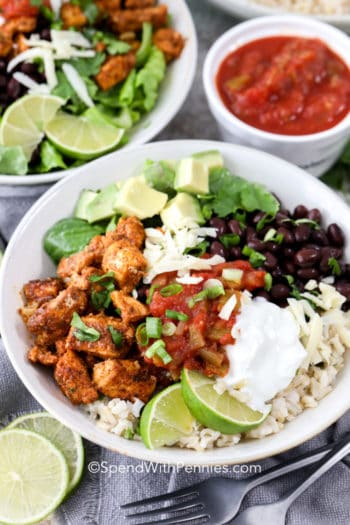 Chicken burrito bowl with green onion sour cream lime wedges and cheese