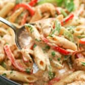 Chicken fajita pasta in a pan with a spoonful being taken out