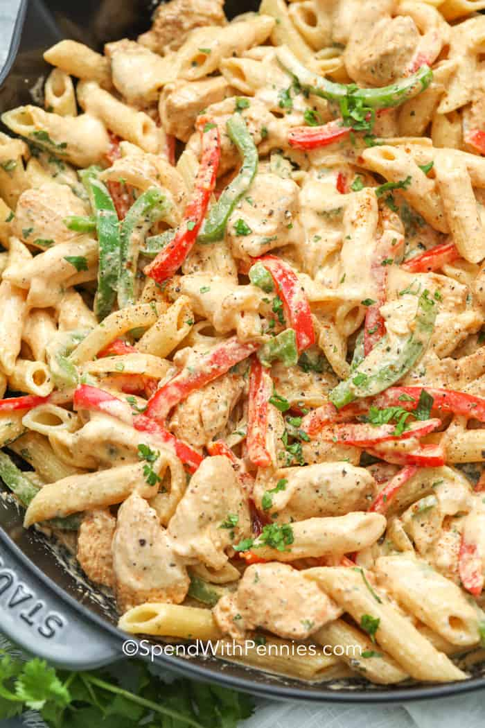 Close up of Chicken Fajita Pasta in a pan, garnished with parsley.