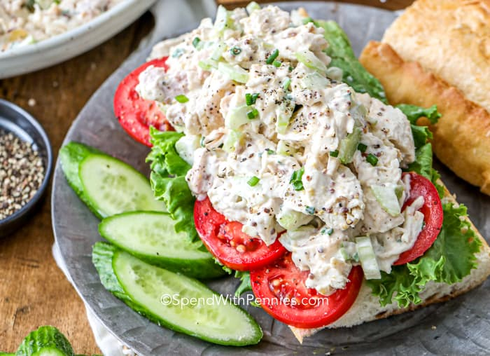 Classic chicken salad with mayonnaise over a roll topped with tomatoes and lettuce