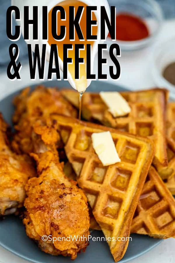 Syrup being poured over fried chicken and waffles.