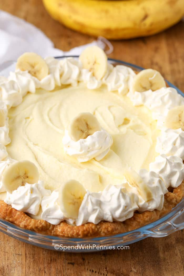 a banana cream pie topped with whipped cream and bananas