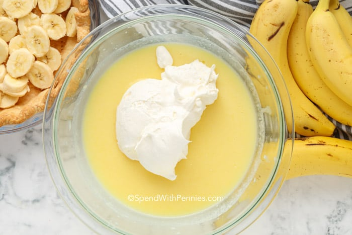 a pie crust with bananas and a bowl of pie filling
