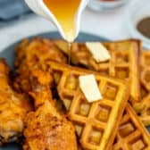 Pouring syrup over Fried Chicken and Waffles