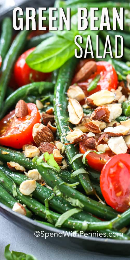 A serving bowl of green bean salad with tomatoes and toasted almonds.