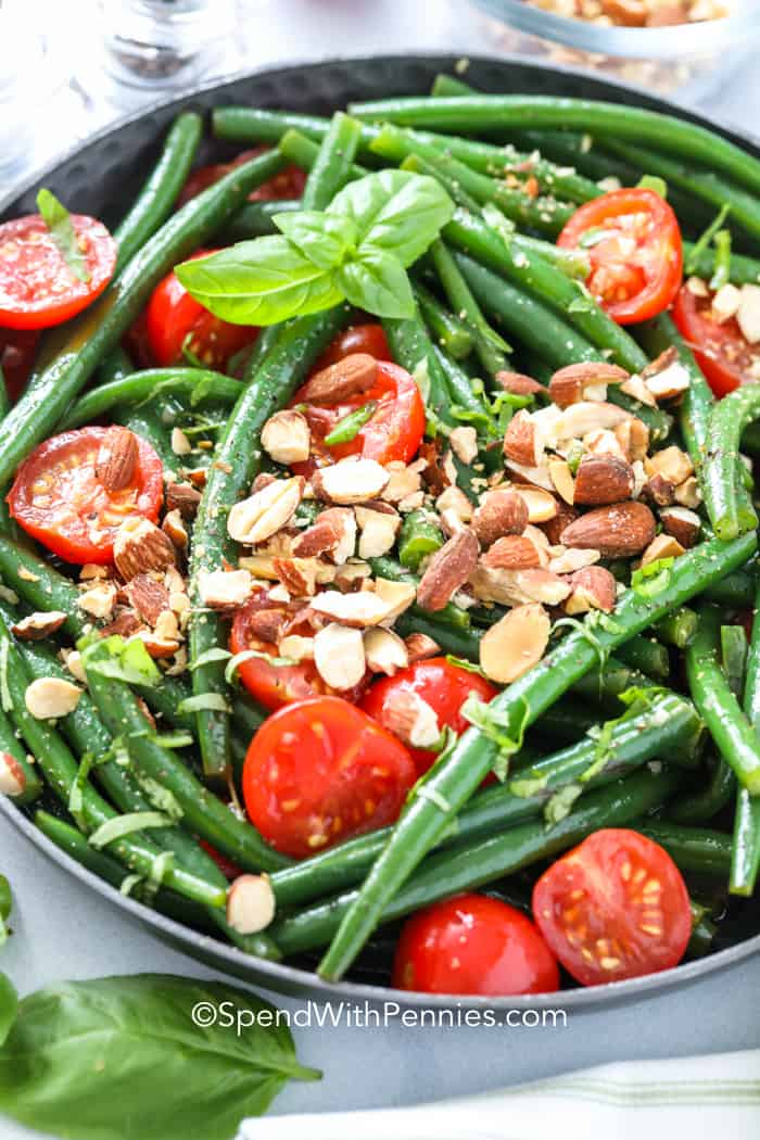 Green bean salad ready to be served topped with almonds in a bowl.
