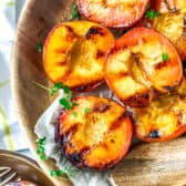 Grilled Peaches in a wooden bowl with a wooden spoon