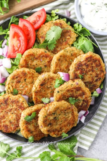 Heard falafels on a plate with tomatoes red onion and cilantro
