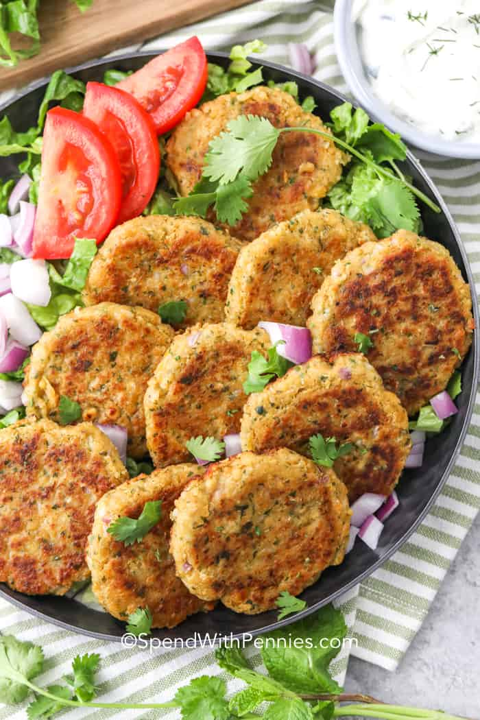 A plate of falafel patties with tomatoes and dip