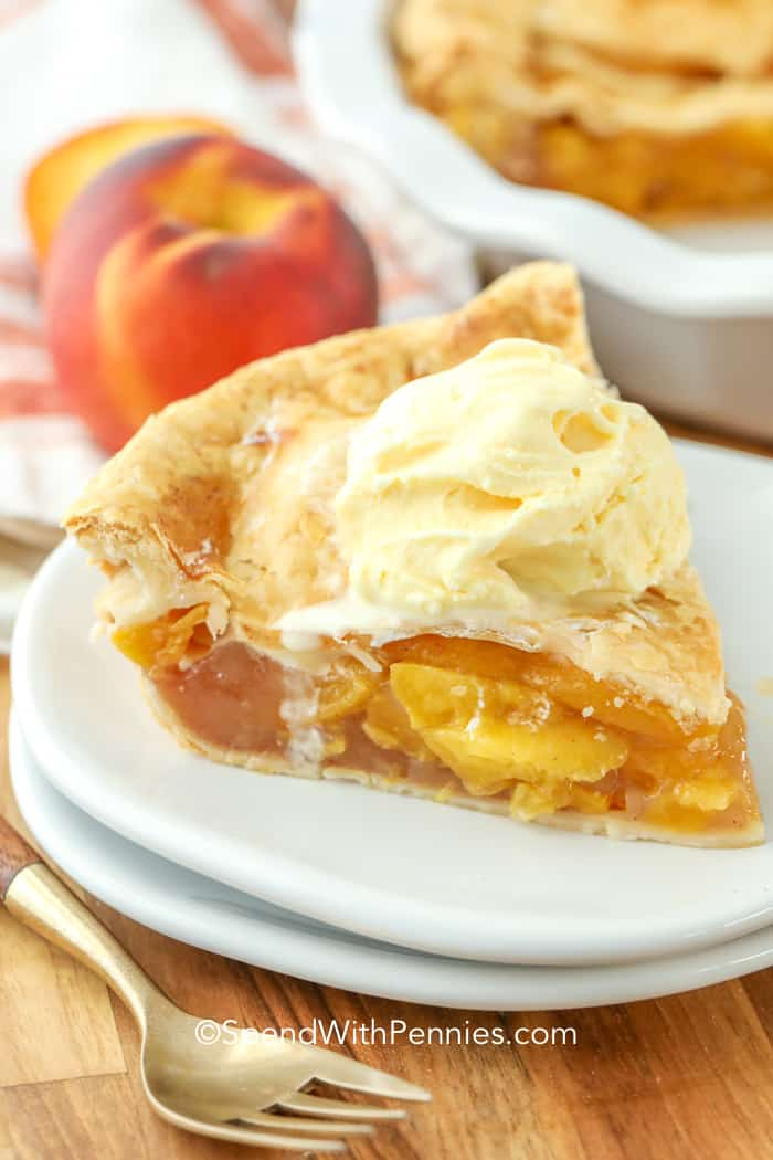 A slice of homemade peach pie with ice cream on top.