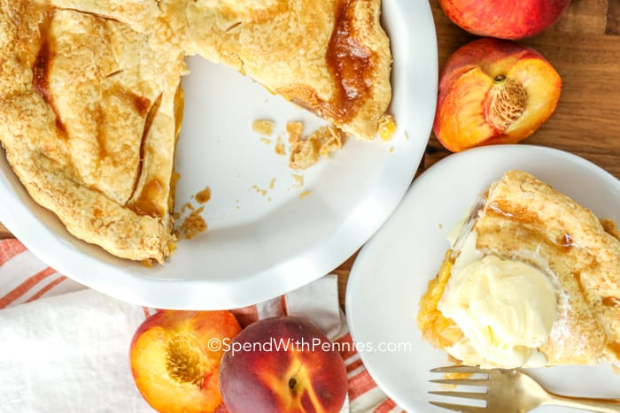 An overview of a peach pie with a slice on the side.
