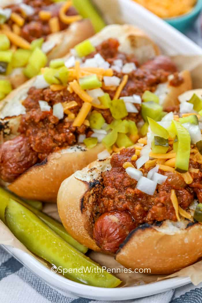 Close up of hot dogs with chili sauce, topped with chopped pickles and shredded cheese.