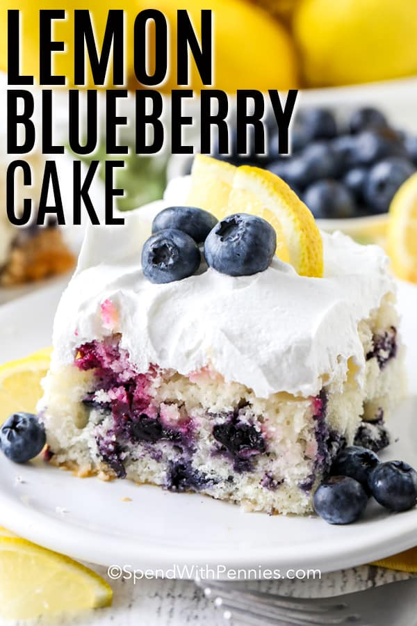 A slice of lemon blueberry cake on a white plate with lemon and blueberry garnish.
