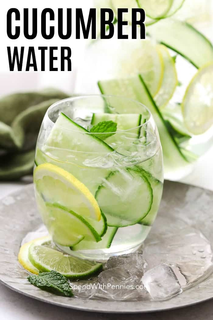 Glass of Cucumber Water with a big jar of it in the background with a title