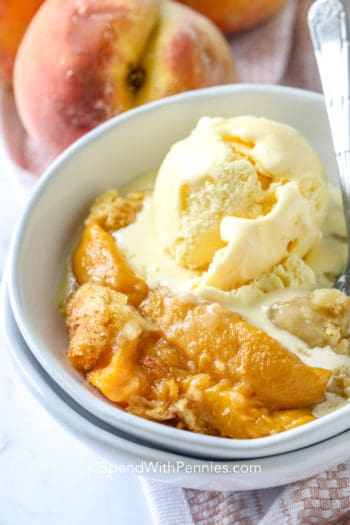 Peach Dump Cake in a white bowl with vanilla ice cream