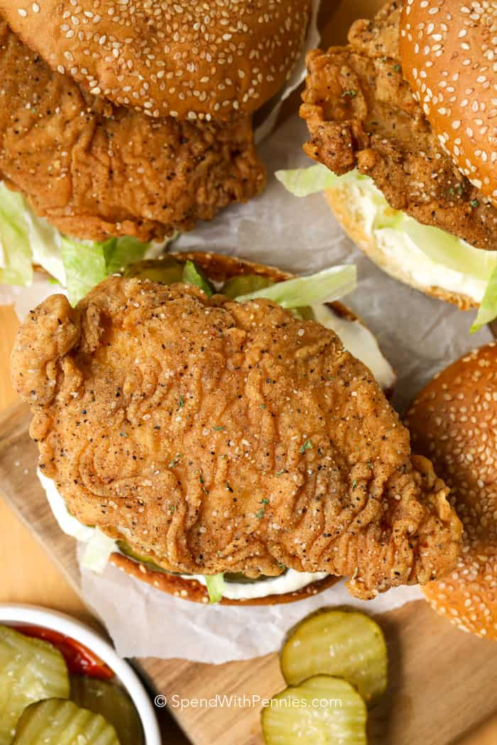 3 crispy chicken sandwiches on sesame seed buns with pickles and lettuce