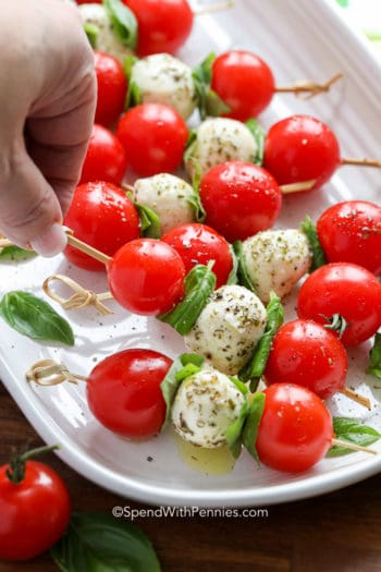 Picking up a Caprese Skewer from serving dish