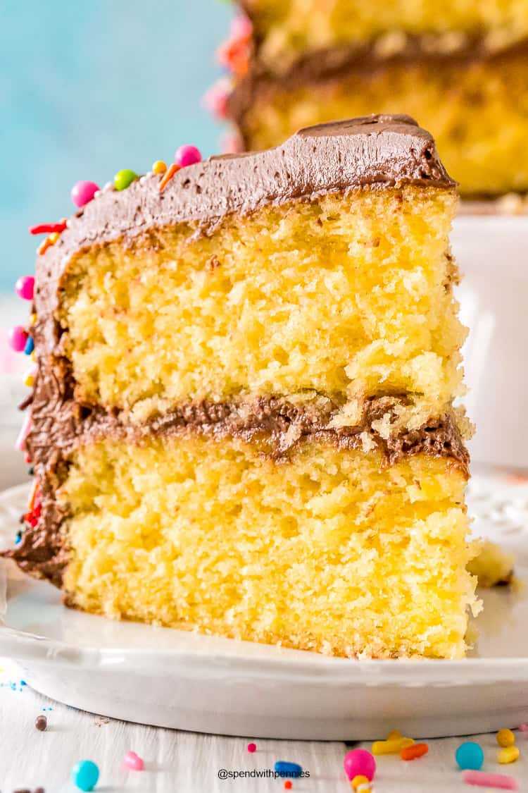 Close up photo of a slice of yellow cake with chocolate frosting on a white plate.