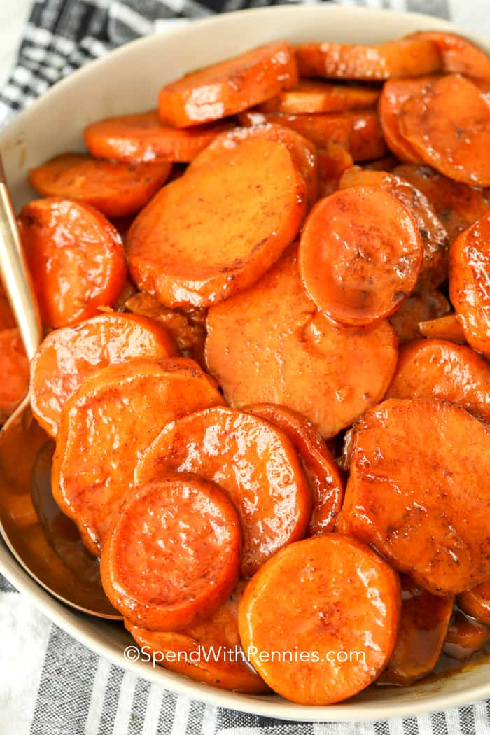 Candied yams in a bowl with a spoon