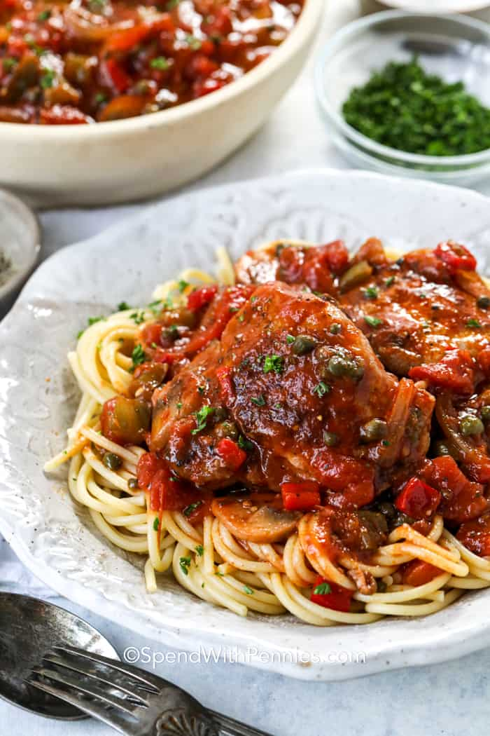 A serving of chicken cacciatore over spaghetti noodles.
