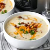 Crock Pot Potato Soup in white bowls with spoons and a crock pot in the background