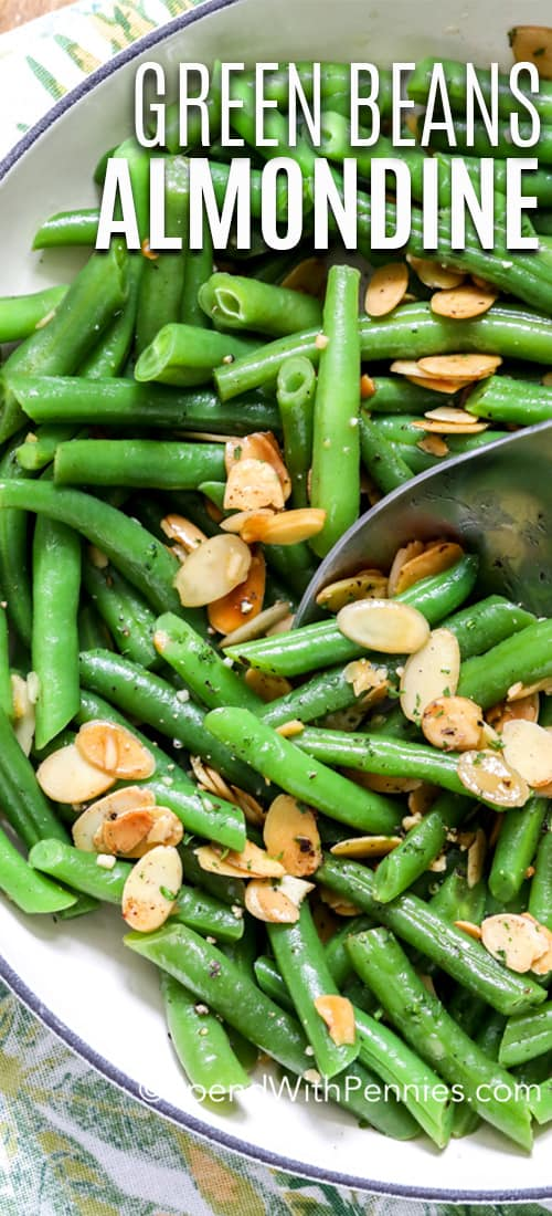 Green beans almondine in a dish with a serving spoon and writing