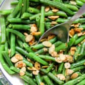 Green bean almondine in a dish with a metal Serving Spoon