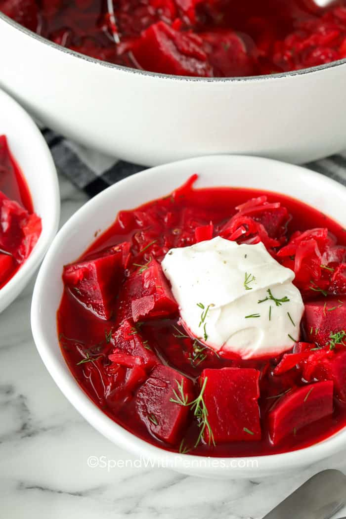 A serving of borscht with a dollop of sour cream on top. Garnished with dill.