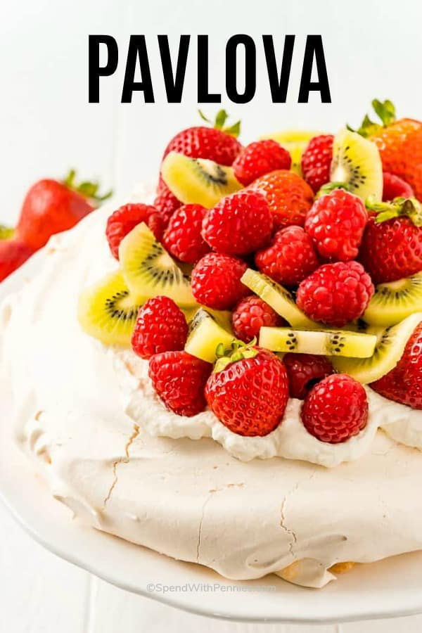 Pavlova on a plate with berries and kiwi with writing