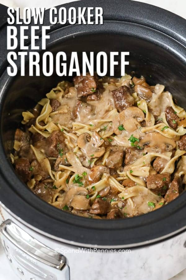 Slow cooker beef stroganoff in a slow cooker with parsley and writing