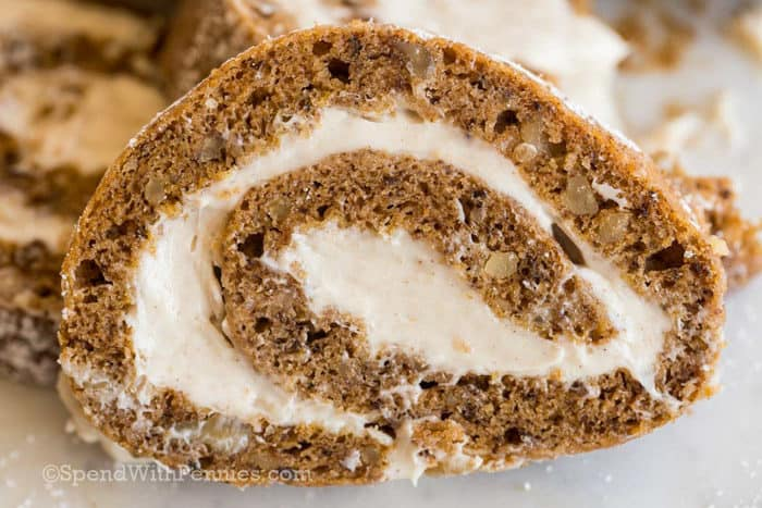 Sliced pumpkin roll on a plate with walnuts and a cream cheese filling.