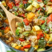 Easy Ratatouille in a pot with a wooden spoon and basil