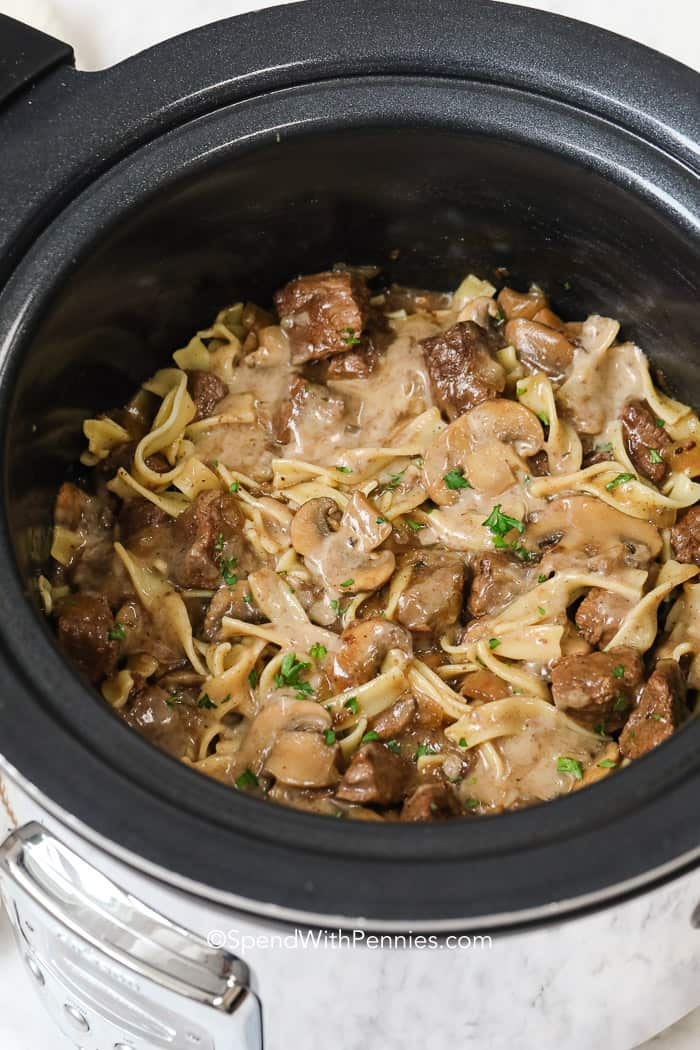 A slow cooker filled with mushroom beef stroganoff ready to serve