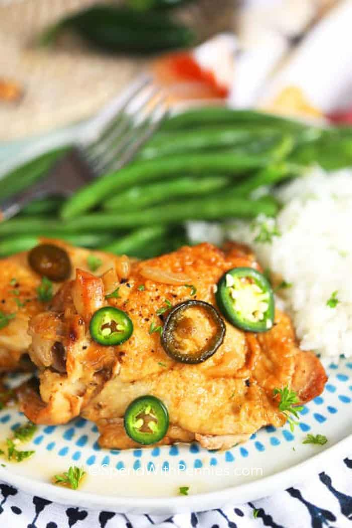 A serving of chicken adobo on a plate with rice and green beans.