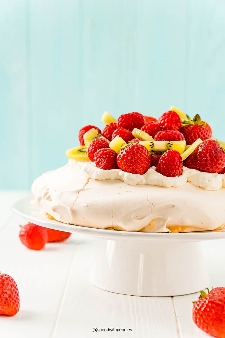 Pavlova on a white cake stand topped with fresh berries and kiwi.
