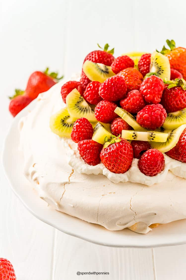 Close up photo of a pavlova topped with strawberries, raspberries, and kiwi on a white cake stand.