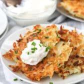 Potato pancakes on a plate garnished with sour cream and chives